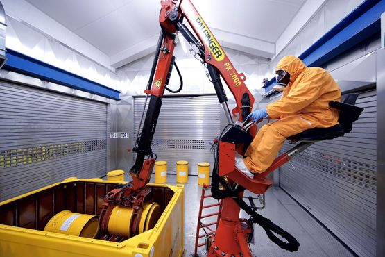 An employee assembles a transport container with waste containers in the interim storage facility Karlsruhe.